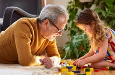 An old White grandfather plays with his granddaughter