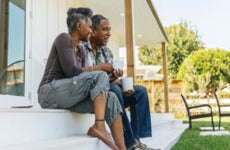 An older Black couple sits on their porch and drinks coffee