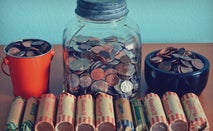 Rolls of coins and loose coins in a jar