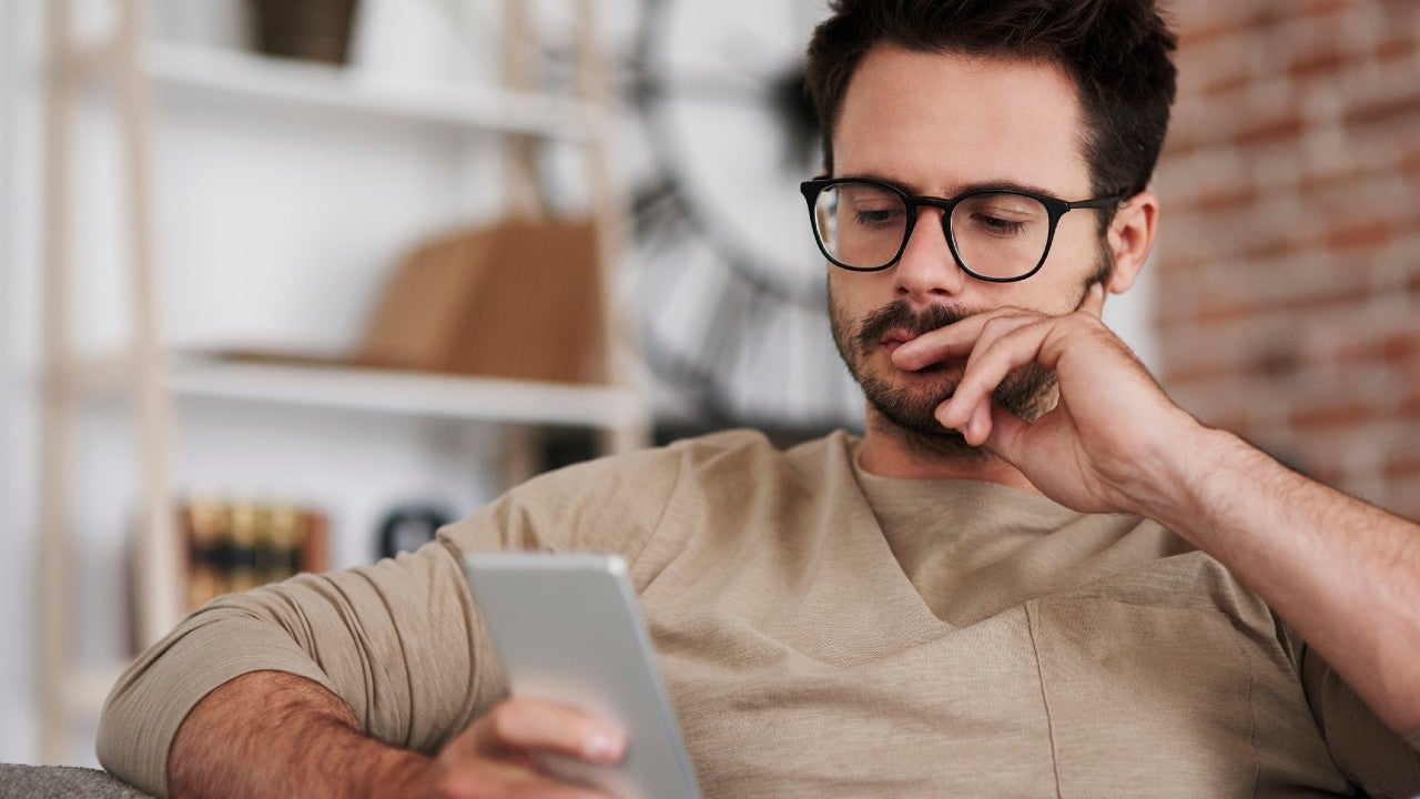 Man looks at cell phone, thinking