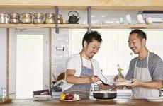 Two men serving pasta