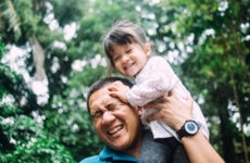 Asian father carries his daughter on his shoulders while they spend some time outside.