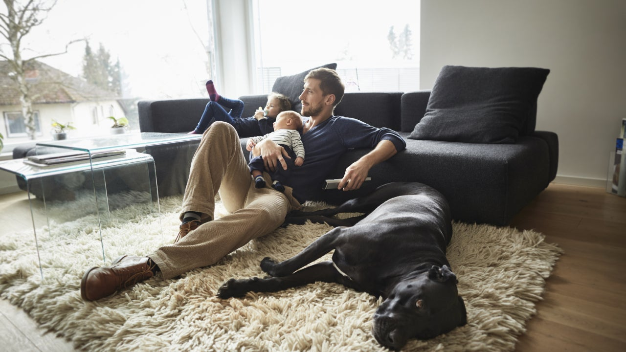 Man sits in the living room on the floor in front of the television with his kids and the family dog.