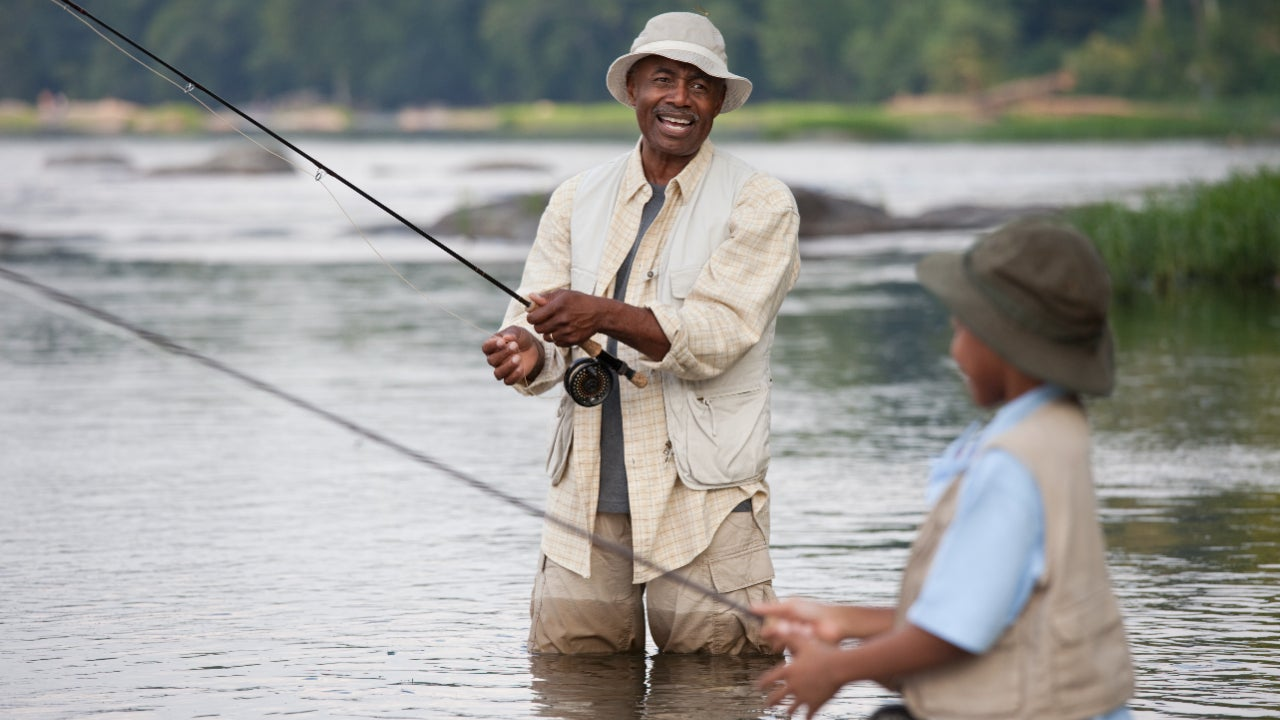 A grandfather and grandson fish in a lake