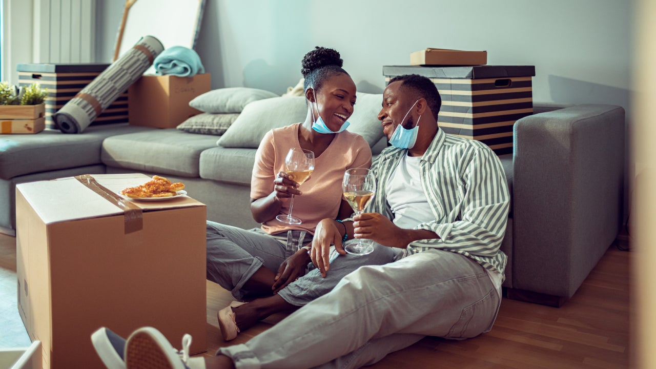 African American couple sits on the floor of their living room in their new house with wine and pizza. They have facemasks pulled down so you can see them smiling.
