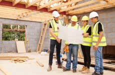 A construction crew evaluates the floor plan of a new home