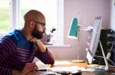 A Black entrepreneur looks over his computer