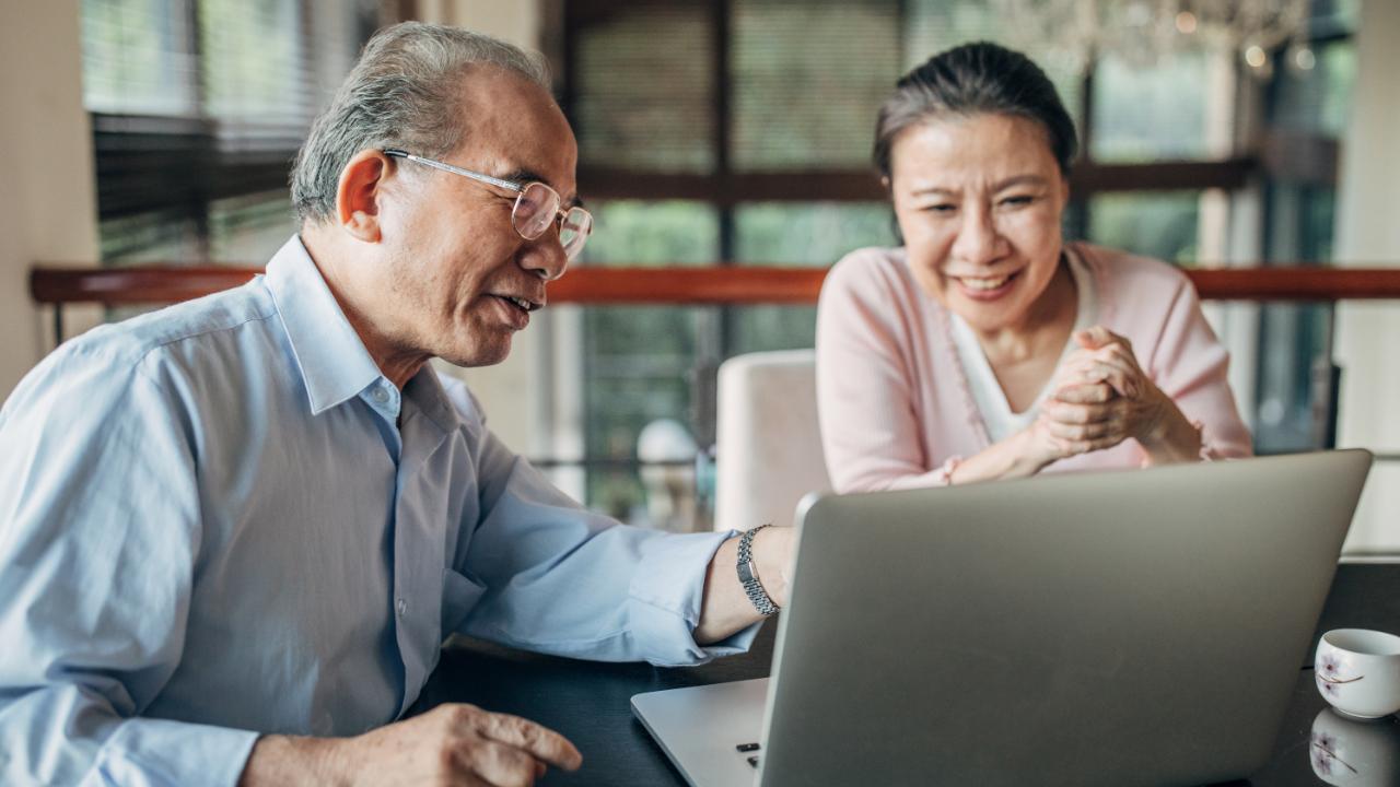 Senior couple looks at laptop