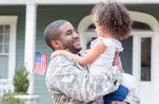 Military father arriving home and hugging child.