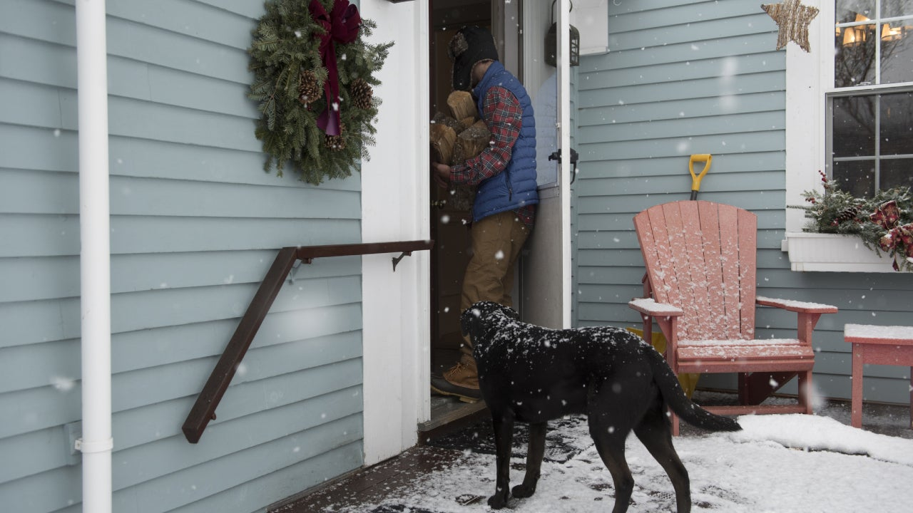 A man holding an armful of chopped wood enters his home while his black dog stands outside on the deck wanting to play. It is snowing.