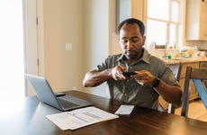 A man sits at his dining room table with his paying his bills and banking using his mobile phone and laptop.