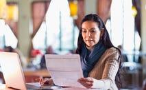 Woman paying bills using laptop.