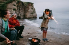 A mixed-race Asian girl stands with her grandparents (one white woman and one Asian man) on the beach playing with a sparkler. It is dusk.