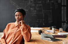 A Black businesswoman sits at a desk