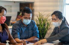 A mask-wearing couple reviews mortgage documents with a mask-wearing advisor.
