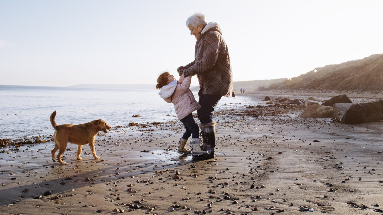 Grandmother plays with her granddaughter on the beach while a dog runs around the shore.