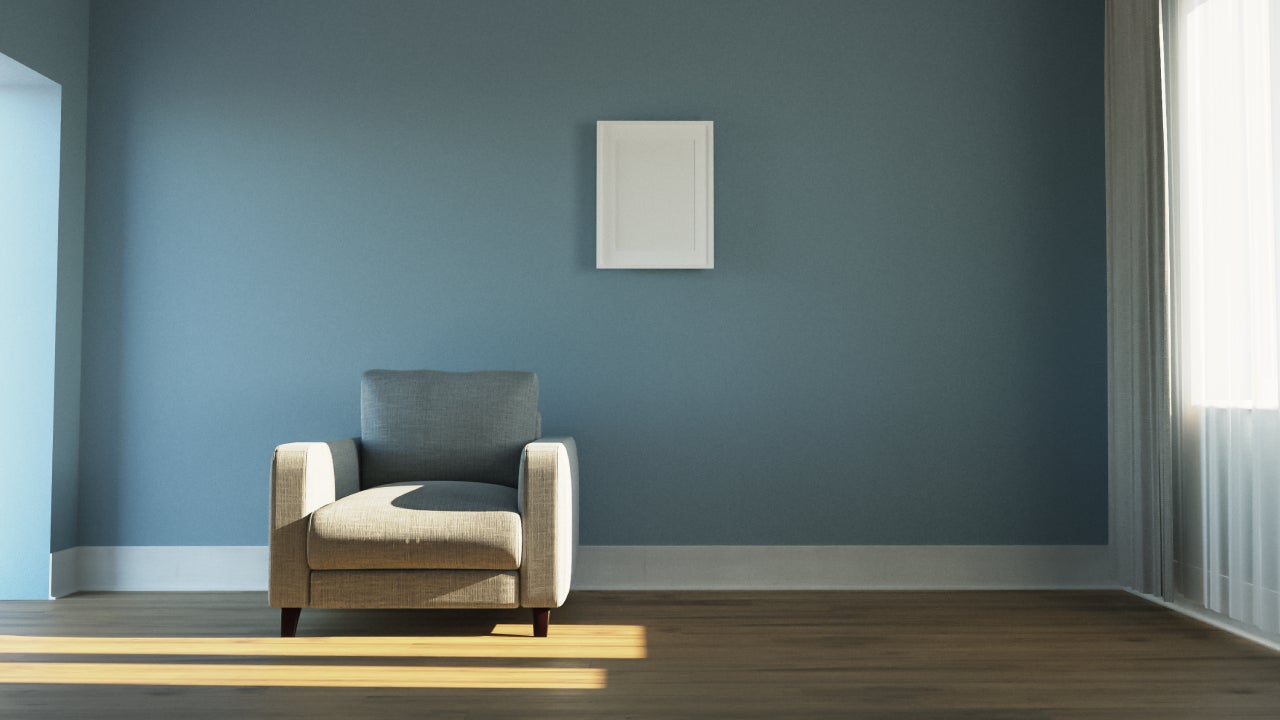 A shot of an empty living room with a blue wall and a white chair.