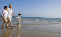 A senior couple of Asians are walking along the beach on a sunny day with their grandson.