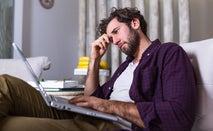 Stressed man looks at laptop
