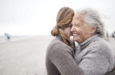 An old mother hugs her adult daughter on a beach.