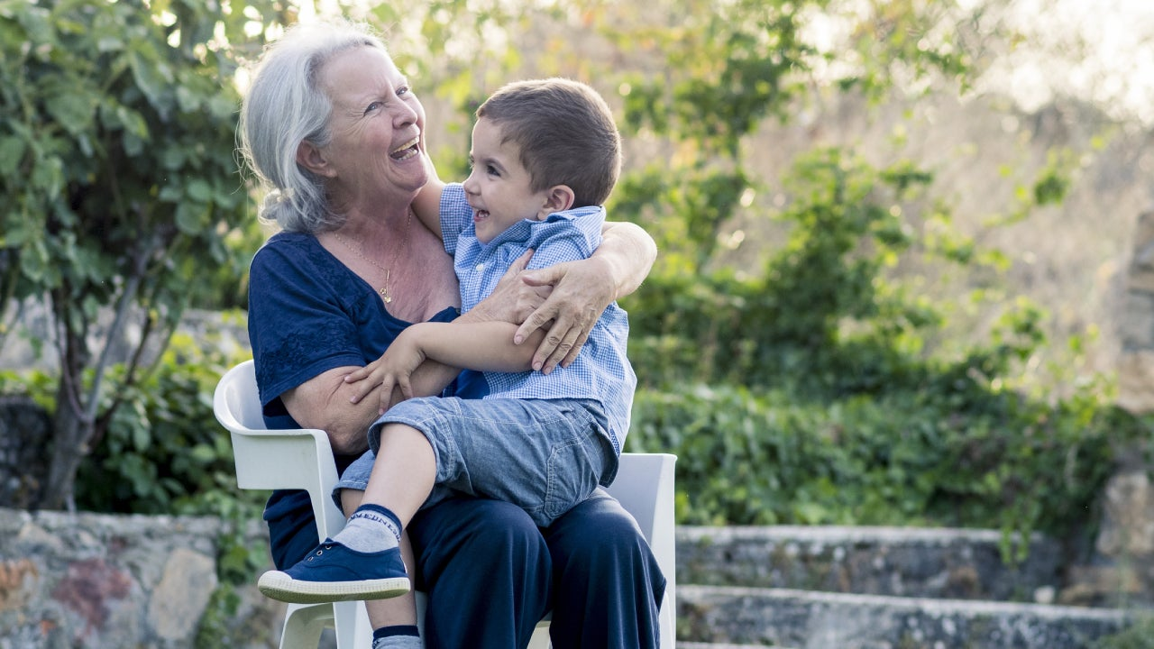 A grandma sits on a chair with her grandson in her lap as they laugh together outside.