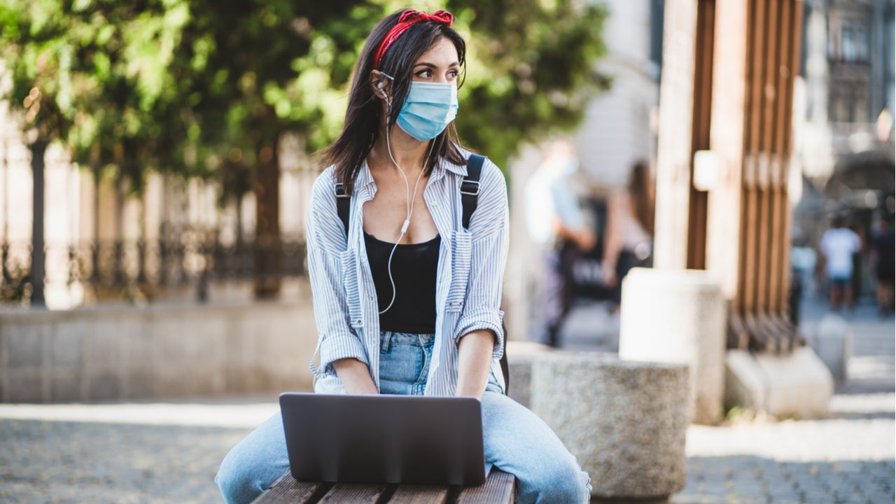 College student sits outside while wearing a mask