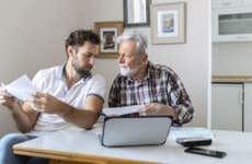 An adult son goes over some policy forms with his father while sitting in front of a laptop.