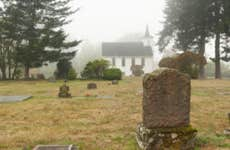 A scenic cemetery outside of an old chapel on a foggy day.