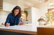 Woman looks over paperwork in a kitchen