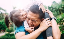 A middle-aged Asian man has his little daughter on his shoulders and they are playing and laughing.