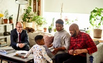 A black couple is sitting together on a couch in the middle of talking to a financial advisor when their son shows up in his pajamas to ask a quesiton.
