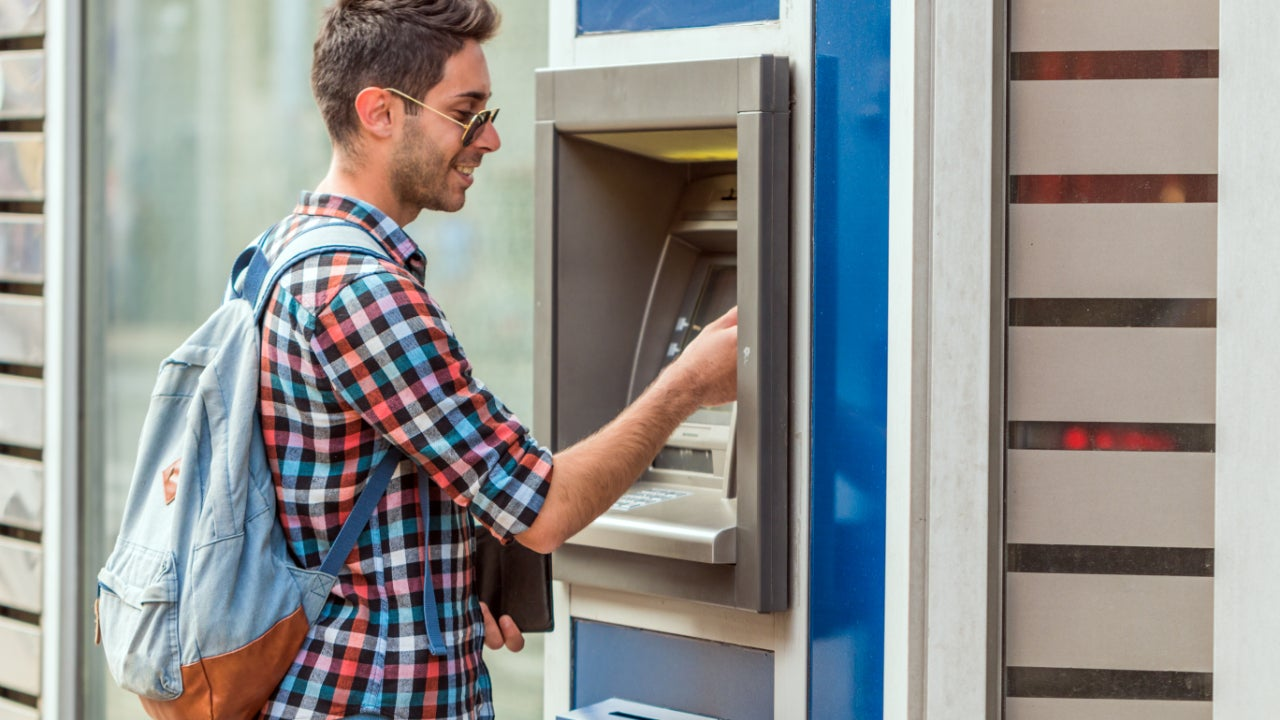 A young man uses an ATM.