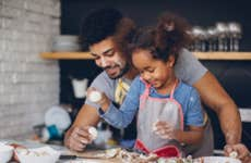 A father and daughter are cooking something together and are making a mess with flower on their clothes and faces.