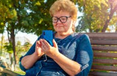 A senior woman goes on her smartphone.
