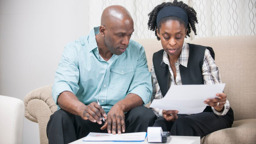 A Black couple reviews financial documents