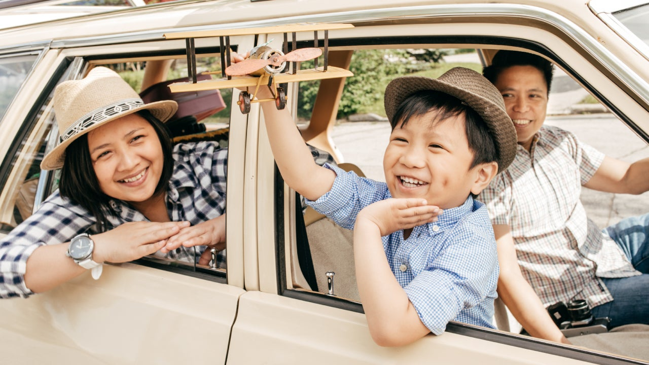 An Asian family going for a drive with the son in the passenger seat holding a toy airplane out the window. (The car is parked).