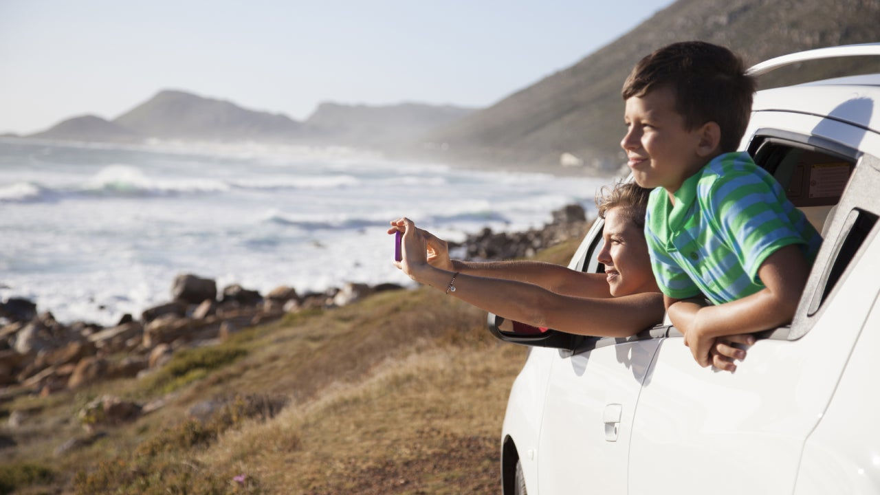 A mother and son leaning out the window of their car on a nice sunny beach.