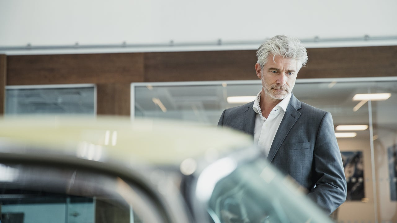 An older gentleman stands in a showroom looking at a car.