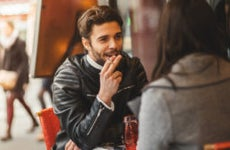 A man and a woman are out at a cafe. The man is holding a cigarette between his fingers.