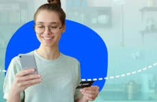 Person looking at phone and holding credit card