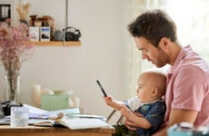 A White father holds his infant son in front of a computer