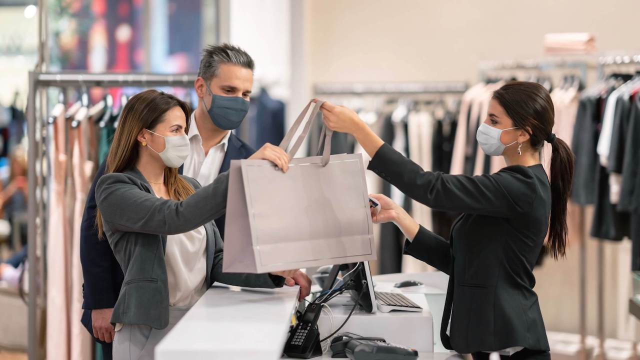 Couple shopping at a clothing store and using facemasks during the pandemic