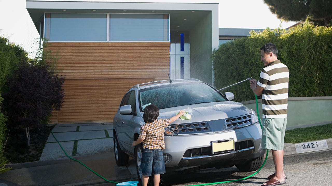 A father and child washing their car in the driveway.