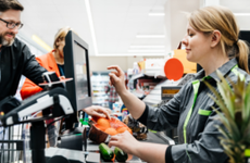 A cashier at a supermarket rings up a customer's items.
