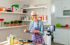 An older White woman prepares a video of her cooking