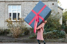 A woman carries an oversized present