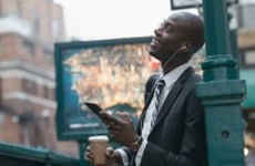A black businessman in New York City listens to a podcast while walking