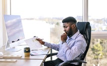 A Black businessman reviewing paperwork.