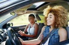 Black daughter drives while her mother is in the passenger side on the phone. They are both laughing and smiling.
