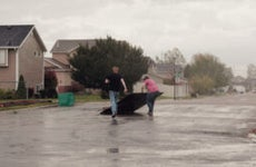 Two men are removing debris from the street after a tornado.